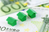 Three green model house and 100 euro banknotes — Stock Photo