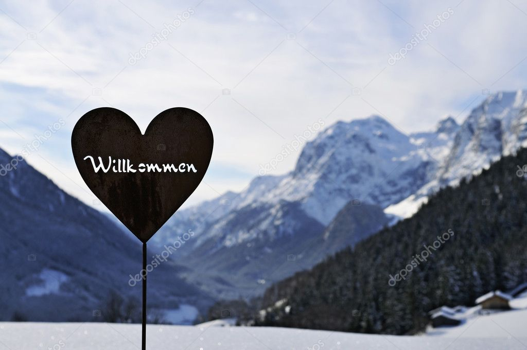 A iron heart shaped welcome sign with white snow covered mountains  in the background, Bavarian Alps, Germany. — Stock Photo #9493588