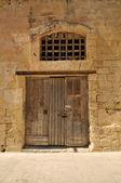 Stare drewniane drzwi w kamiennym murem — Zdjęcie stockowe