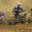 Group Quad motorbike racers in the dust shrouded — Stock Photo