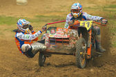 Sidecar riders in the turn. From motorcycles flies mud. — Stock Photo