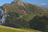 Para-glider, which started to fly with a red parachute in the Dolomites — Stock Photo