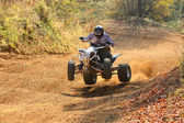 ATV rider goes up the hill — Stock Photo
