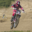 Stock Photo: Motorbike rader in red jumps.