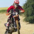 Stock Photo: Rider jumps with motorbike. front wheel is wound in side