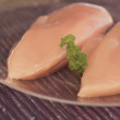 Chicken breast on a transparent plate ready to cook. - Photo