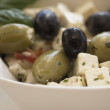 Salad of olives, served with chunks of cheese in a white bowl. - Stockfoto