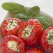 Spicy round red peppers stuffed with cheese in the white bowl. - Stockfoto