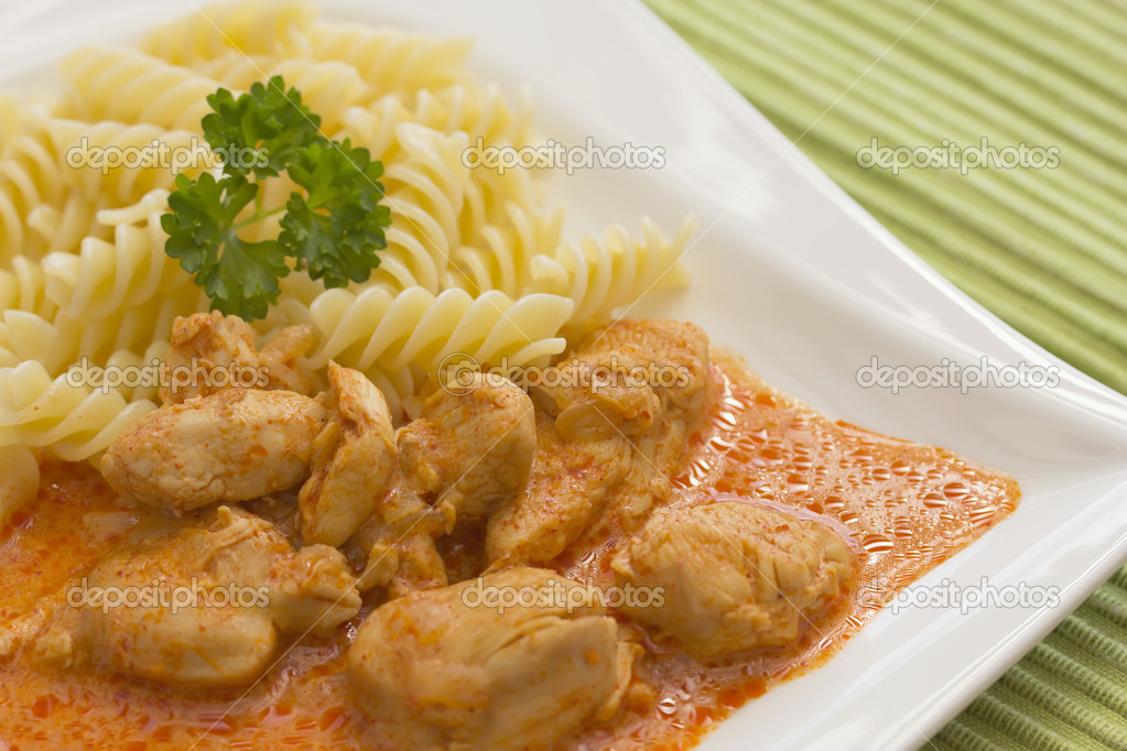 Chicken pieces with Pasta in Paprika Cream Sauce. Decorated with parsley.  Stock Photo #9842280