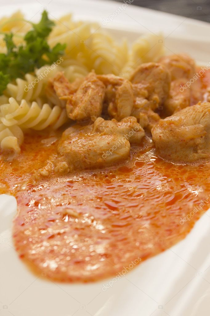 Chicken pieces with Pasta in Paprika Cream Sauce. Decorated with parsley. Vertically. — Stock Photo #9842286