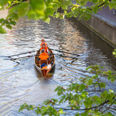 Typical orange dressed dutchmen in a boat on Queen's Day — Stock Photo