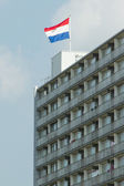 Dutch flag on top of a block of flats against the blue sky — Stock Photo
