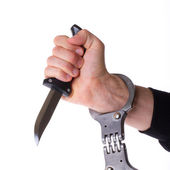 Male with a sharp knife in it's hand with a handcuff — Stock Photo