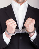 Man with handcuffs, business suit, focus on the handcuffs — Stock Photo
