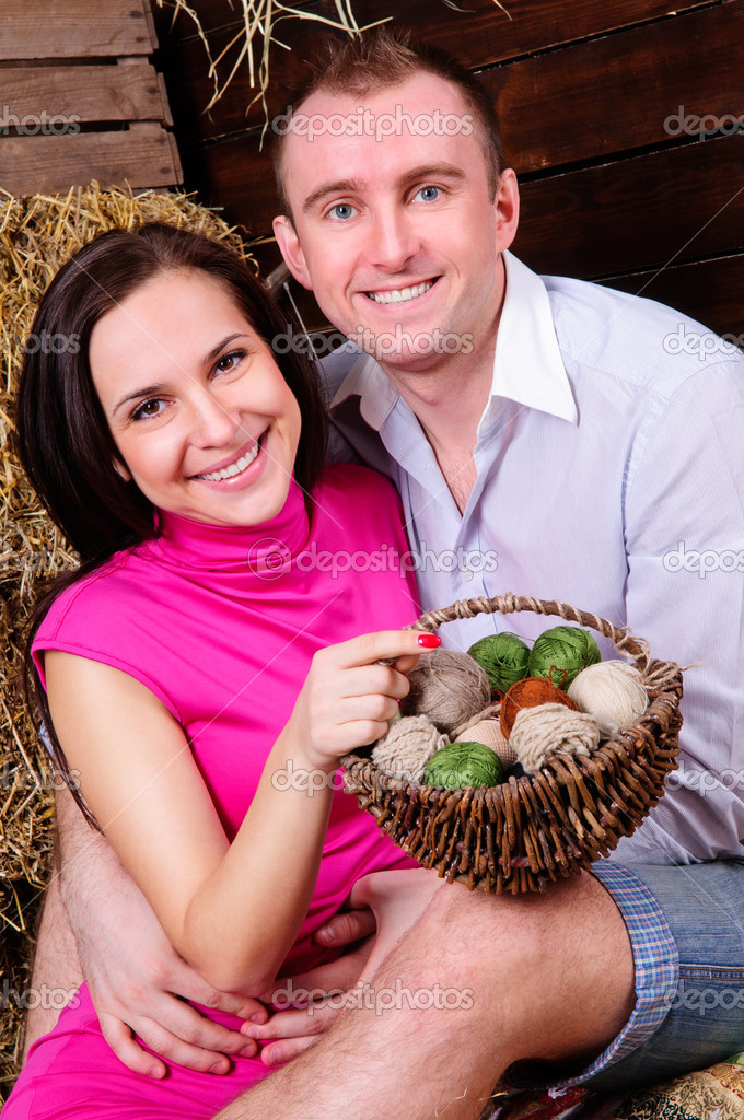 Young love the family, a man and a woman smiling at the camera. in a barn on straw — Stock Photo #10065629