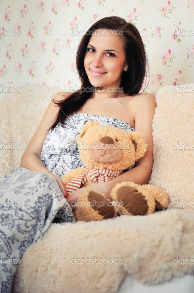 Woman on couch with toy bear  Stock Photo #9578542