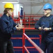 Two workers talking in a factory — Stock Photo