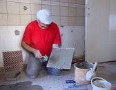 Senior Man decorating with ceramic tiles — Stock Photo