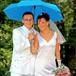 Bridegroom and bride with the umbrella — Stock Photo