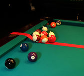 Pool table and balls with red ribbon — Stock Photo