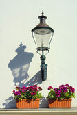 Outdoor lantern on white wall and pots with flowers. — Stock Photo