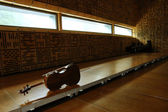 Violoncello laying on the floor in empty classroom — Stock Photo