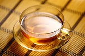 Cup of tea on straw tablecloth — Stock Photo