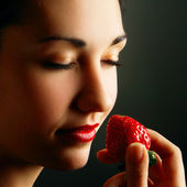 Woman smelling strawberry — Stock Photo