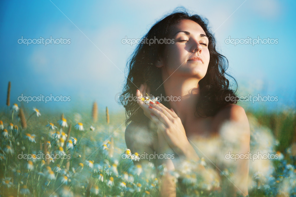 Portrait of a girl with closed eyes between camomiles in the field against blue sky — Stock Photo #9591176