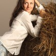 Charming young smiling woman posing near the haystack — Stock Photo #9419657