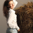 Charming young smiling woman posing near the haystack — Stock Photo