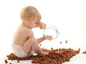 Baby playing with hazelnuts — Stock Photo