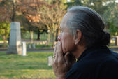 Man sitting at gravesite — Stock Photo