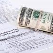 A roll of USD cash near an IRS tax form — Stock Photo