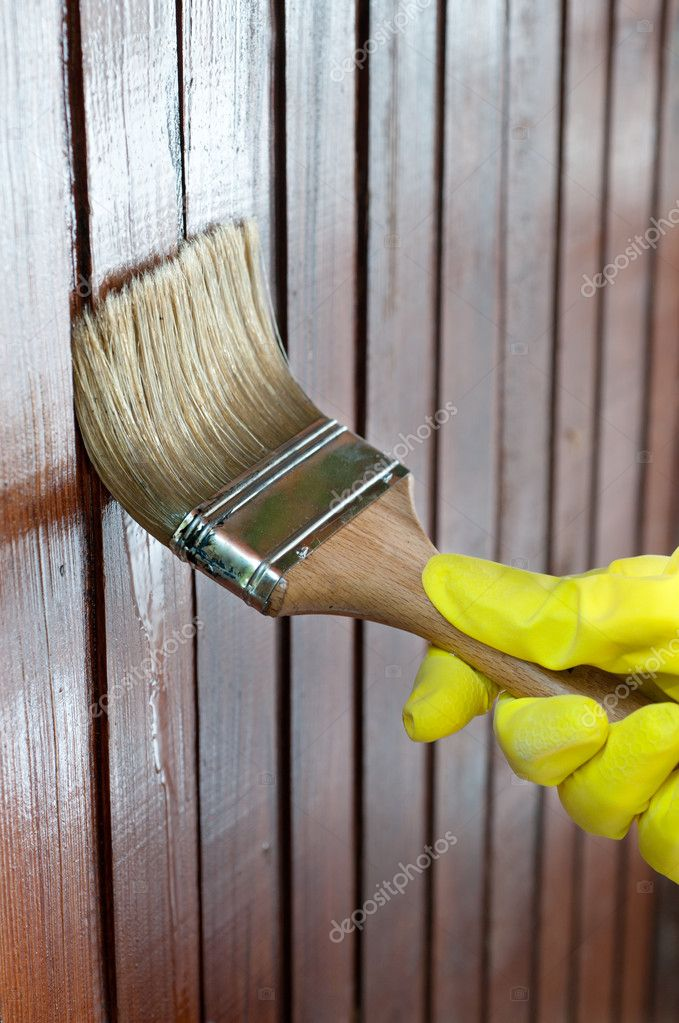 Maintaining of wooden surfaces with fresh protective paint...  Stockfoto #10041826