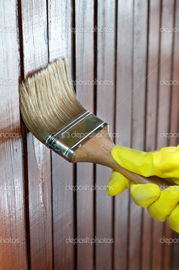 Maintaining of wooden surfaces with fresh protective paint... — Lizenzfreies Foto #10041826