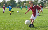 Boy kicking football — Stock Photo