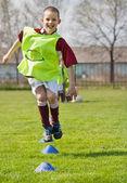 Niño saltando en el campo de fútbol — Foto de Stock