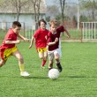 Boys kicking ball - Stockfoto