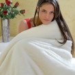 Girl sitting wrapped in a blanket — Stock Photo