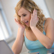 Young woman with surprised facial expression working at laptop — Stock Photo