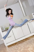 Woman jumping in kitchen — Stock Photo