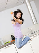 Young woman jumping in her kitchen — Stock Photo