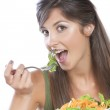 Young caucasian brunette eating vegetable isolated on white — Stock Photo