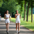 Two young woman running in a park — Stock Photo
