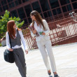 Two businesswoman walking outdoors — Stock Photo