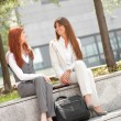 Two businesswoman talking outdoors in the shade — Stock Photo
