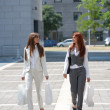 Two young woman with shopping bags outdoors — Stock Photo