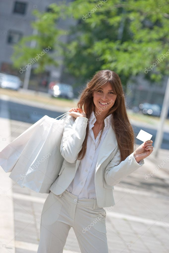 Young caucasian woman,showing a card while holding shopping bags — Stock Photo #9766361