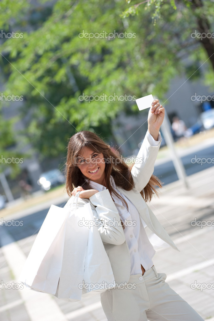 Young caucasian smiling woman,show a blank credit or business card holding shopping bacgs on her shoulders  Stock Photo #9766443